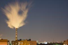 La cheminée d'usine émet de la vapeur au-dessus de la ville Photos stock