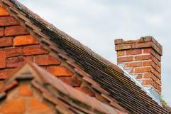 La cheminée endommagée a besoin de l'extérieur de construction de vieux dessus de toit de réparation Photographie stock
