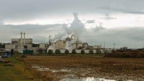 La cheminée d'évacuation des fumées et les tuyaux d'usine soufflent dans l'air banque de vidéos