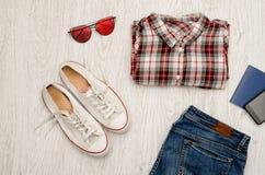 La chemise à carreaux rouge et blanche, verres, espadrilles, jeans, téléphonent a Image stock