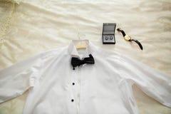 La chemise blanche, l'anneau, et la montre du bébé s'habillant sur le lit Chemises classiques du ` s d'hommes sur le lit photographie stock libre de droits