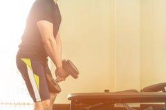La chemise noire des hommes soulèvent des haltères photographie stock