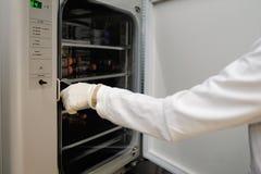 La chercheuse de femmes avec la longs chemise de douille et tube et équipement de collecte de gants du coffret pour faire l'essai image stock