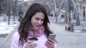 La chiacchierata, ragazza sta sedendosi in Internet con il telefono cellulare con la tazza di plastica nella mano in città