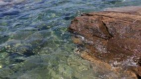La chiara acqua del mar Egeo lava le rocce sopra stock footage