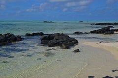 La chiara acqua di mare trasparente pulita fuori da Ile Cerfs aus. Mauritius con le rocce nere emergenti e la spiaggia sabbiosa v Fotografie Stock Libere da Diritti