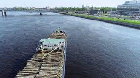 La chiatta con legno sta tirando sul grande fiume blu attraverso la città con il ponte archivi video