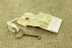 La chiave al concetto di felicità su fondo rustico Fotografia Stock Libera da Diritti