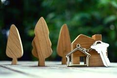 La chiave con il keychain della casa e di legno domestici treen ed a casa deridono su su fondo di legno d'annata, concetto della  fotografie stock