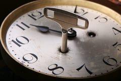 La chiave d'avvolgimento è inserita nel fronte dell'orologio fotografie stock libere da diritti