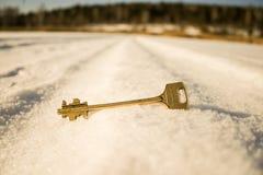 La chiave dorata alla porta si trova nella neve immagine stock libera da diritti