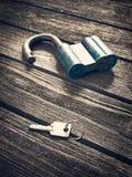 La chiave e fissa il fondo di legno Immagine Stock