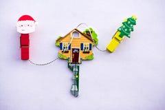 La chiave sotto forma di una casa su un fondo bianco con la molletta da bucato di Natale taglia di legno decorativo Immagine Stock