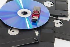 La chiavetta USB rossa messa sul CD ed ha disket sotto loro Immagini Stock Libere da Diritti