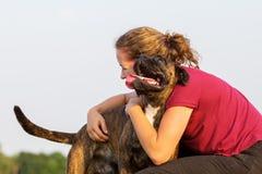 La chica joven abraza su perro del boxeador Fotografía de archivo