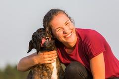 La chica joven abraza su perro del boxeador Foto de archivo libre de regalías