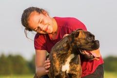 La chica joven abraza su perro del boxeador Imágenes de archivo libres de regalías