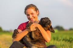 La chica joven abraza su perro del boxeador Fotos de archivo libres de regalías