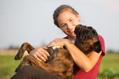 La chica joven abraza su perro del boxeador Imagen de archivo