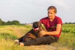 La chica joven abraza su perro del boxeador Fotos de archivo
