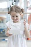 La chica joven abre la caja blanca y mira en ella Imagen de archivo