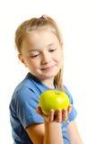 La chica joven admira la manzana Imagen de archivo libre de regalías