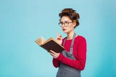 La chica joven agradable con los bigudíes y los vidrios se zambulló en la lectura Foto de archivo