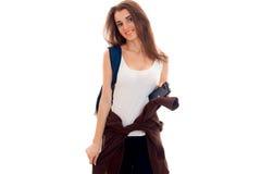 La chica joven alegre en una camiseta blanca mira en la cámara y ata las manos de la chaqueta Foto de archivo