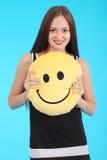 La chica joven alegre está sosteniendo una almohada sonriente de la cara Foto de archivo