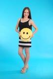 La chica joven alegre está sosteniendo una almohada sonriente de la cara Imágenes de archivo libres de regalías