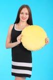 La chica joven alegre está sosteniendo una almohada sonriente de la cara Foto de archivo libre de regalías