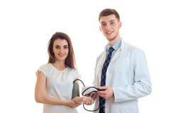 La chica joven alegre se coloca con el tonometer en el brazo al lado del delantal sonriente del doctor Foto de archivo libre de regalías