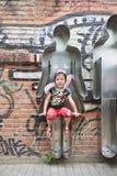 La chica joven alegre se sienta en un trabajo de arte en el área de 798 artes, Pekín, China Foto de archivo