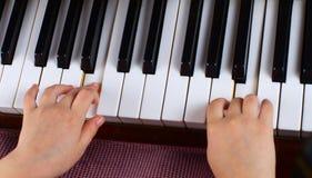 La chica joven aprende jugar un piano Fotografía de archivo
