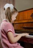 La chica joven aprende jugar un piano Imagen de archivo libre de regalías