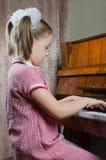 La chica joven aprende jugar un piano Fotos de archivo libres de regalías
