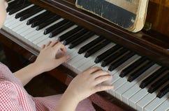 La chica joven aprende jugar un piano Imagen de archivo