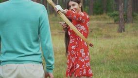 La chica joven apunta su arco en hombre metrajes