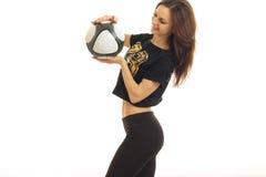 La chica joven atlética coloca sonrisas oblicuas y sostener un balón de fútbol Fotografía de archivo libre de regalías