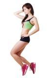 La chica joven atlética en pantalones cortos de la camiseta y del cortocircuito realiza un ejercicio. Imagen de archivo