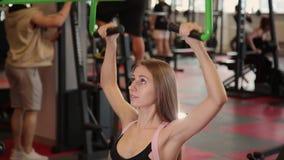 La chica joven atlética hermosa realiza un tirón en el simulador del pecho en el gimnasio metrajes