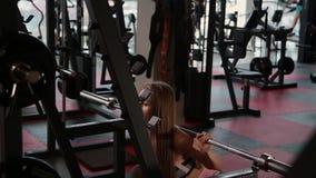 La chica joven atlética hermosa se agacha en los hombros en el gimnasio metrajes
