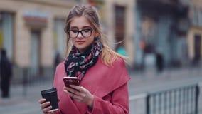 La chica joven atractiva con el corte de pelo casual que sostiene una taza de café caliente y que usa su teléfono celular para ma almacen de metraje de vídeo