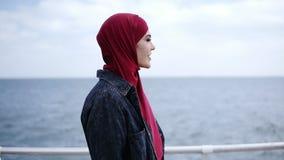 La chica joven atractiva con el hijab en su cabeza está caminando supuesto cerca del lado de mar con las gaviotas que vuelan en metrajes