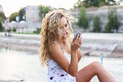 La chica joven atractiva con el pelo rubio rizado que la comprueba hace U Imagenes de archivo
