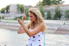 La chica joven atractiva con el pelo rubio rizado que la comprueba hace U Fotografía de archivo