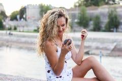 La chica joven atractiva con el pelo rubio rizado que la comprueba hace U Imagen de archivo libre de regalías