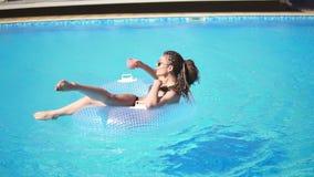 La chica joven atractiva con las gafas de sol, coctail y teme en el anillo de goma inflable que presenta en la piscina almacen de metraje de vídeo