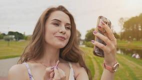La chica joven atractiva con una sonrisa en su cara en un vestido del verano en un parque colorea sus labios que miran la pantall almacen de metraje de vídeo