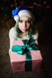 La chica joven atractiva da el regalo debajo del árbol de navidad Foto de archivo libre de regalías